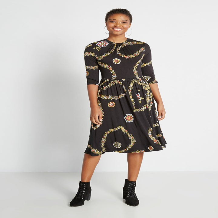 model wearing a 3/4-sleeve black crewneck dress in black with floral garland print