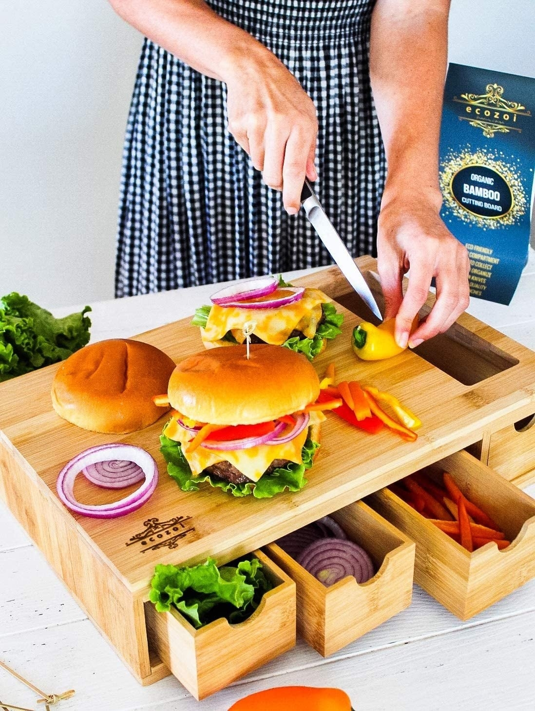 Model uses the bamboo cutting board to store vegetables as they prepare a burger