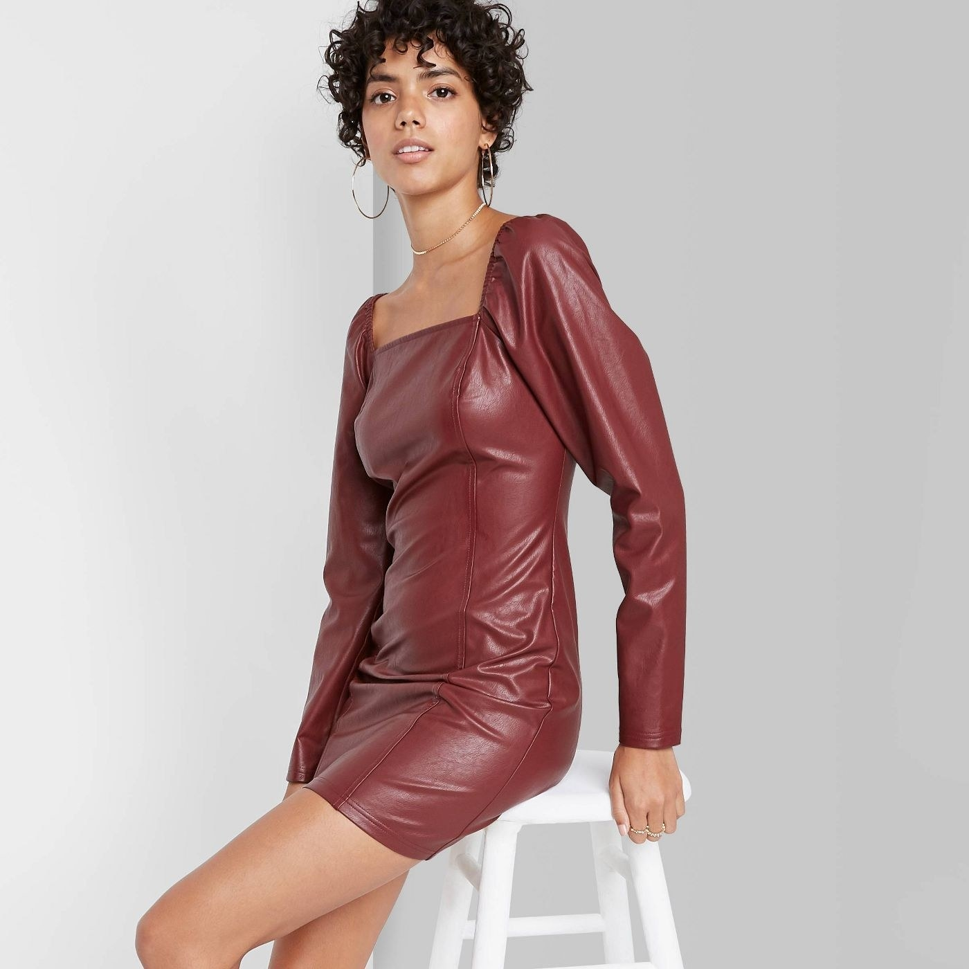 Model in red faux leather dress