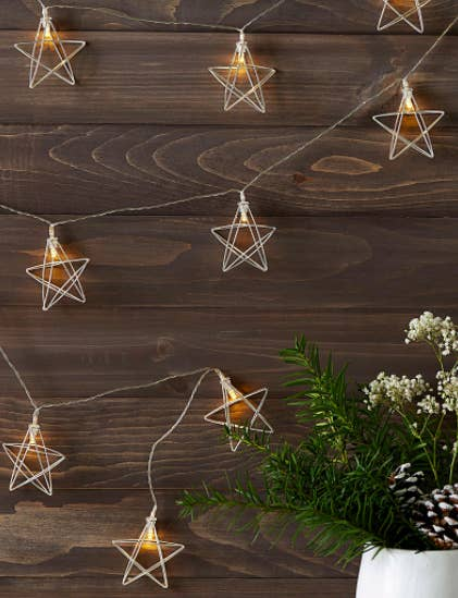 A set of wire star string lights on a wooden surface
