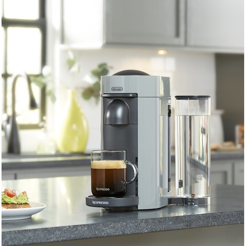a cup of coffee sitting on a grey coffee maker on a counter
