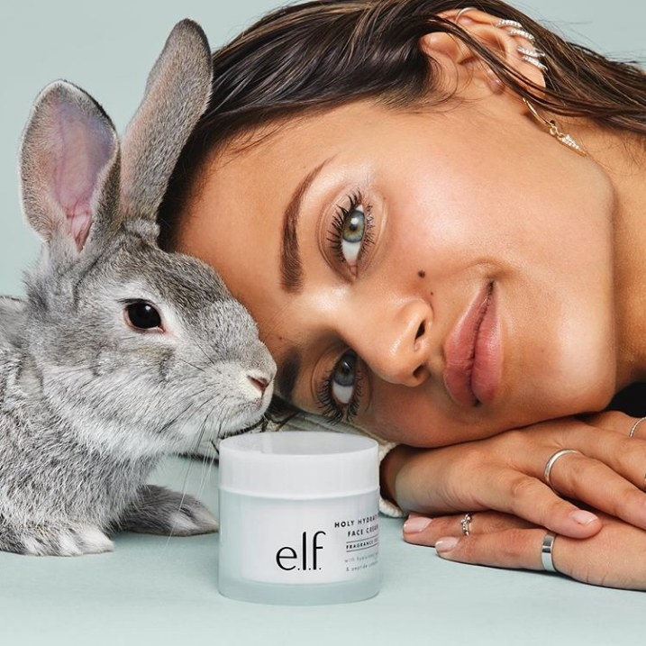 Model and bunny pose beside a light blue container of face cream with black letters