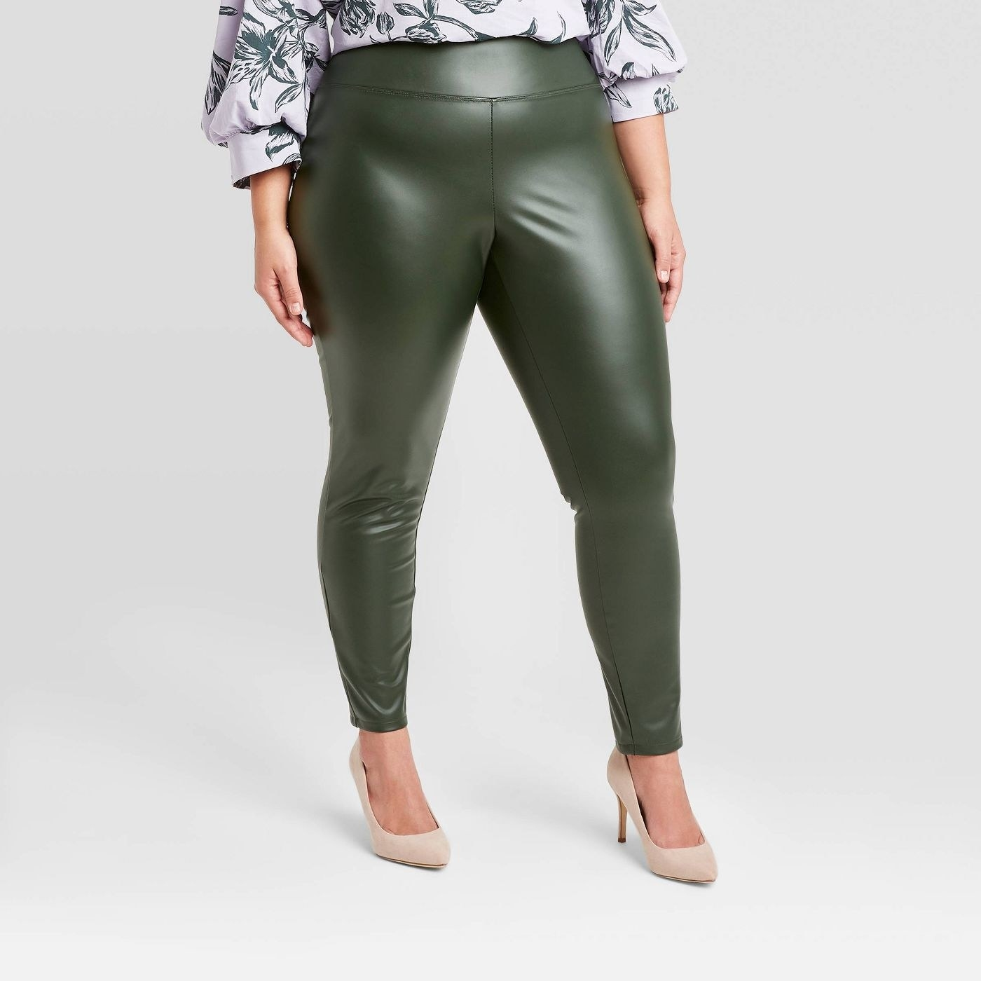 Model in green faux leather leggings