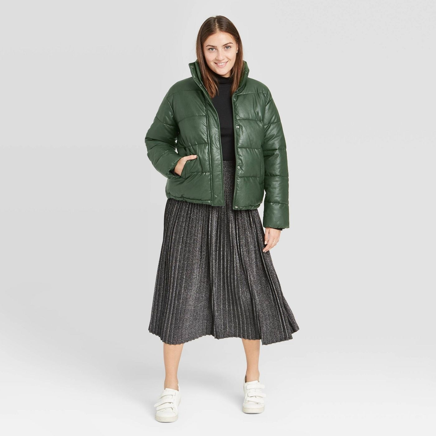 Model in green leather puffer and black skirt