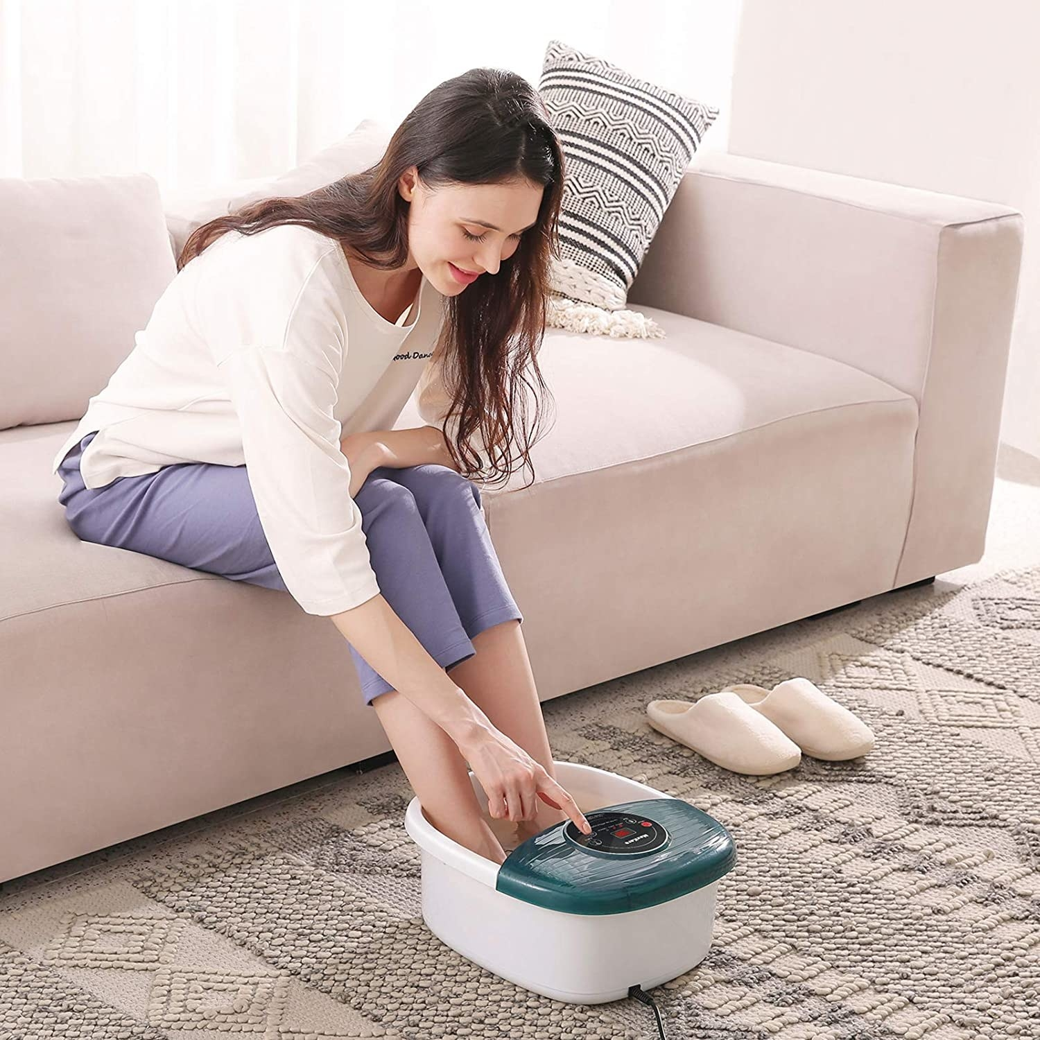 Model presses button on top of green and white foot bath massager while sitting on a couch