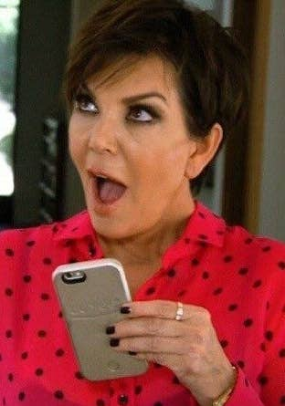 Kris Jenner holding a phone with a look of surprise on her face