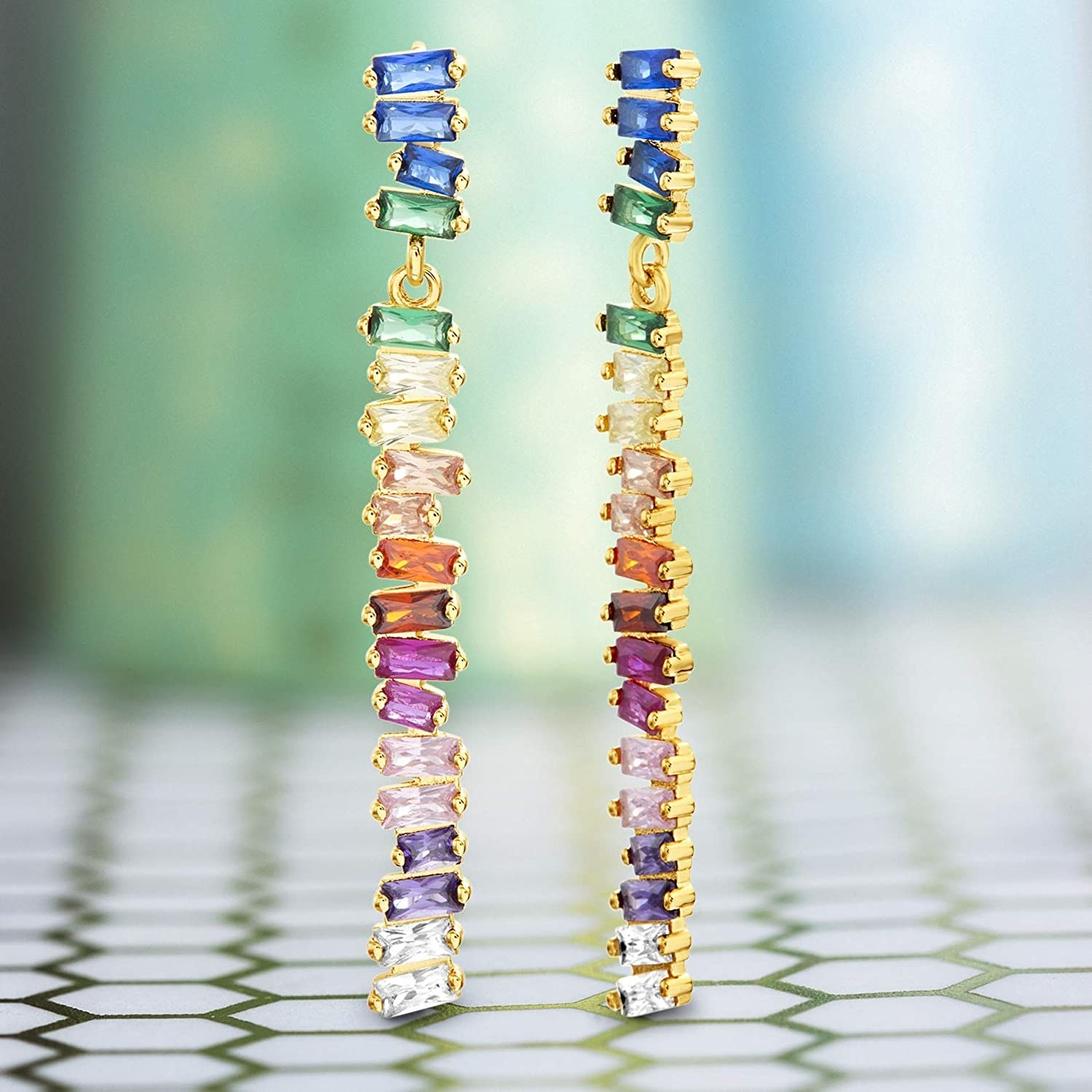 the earrings, which are a long-skinny stacks of two stones per color all stacked on top of one another with gold trim
