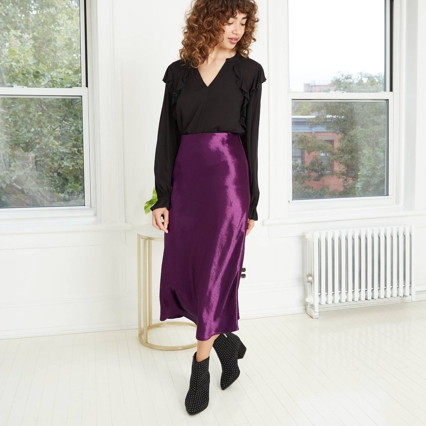 Moden in purple silky maxi skirt and black top
