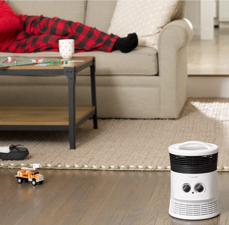 White round space heater on wooden living room floor
