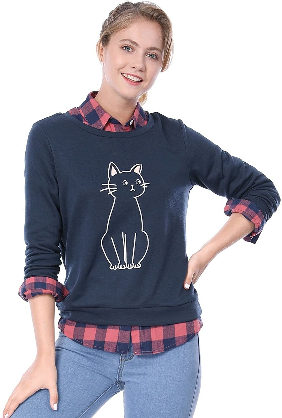 A model wearing the navy sweatshirt with a drawing of a cat on it layered over a plaid shirt