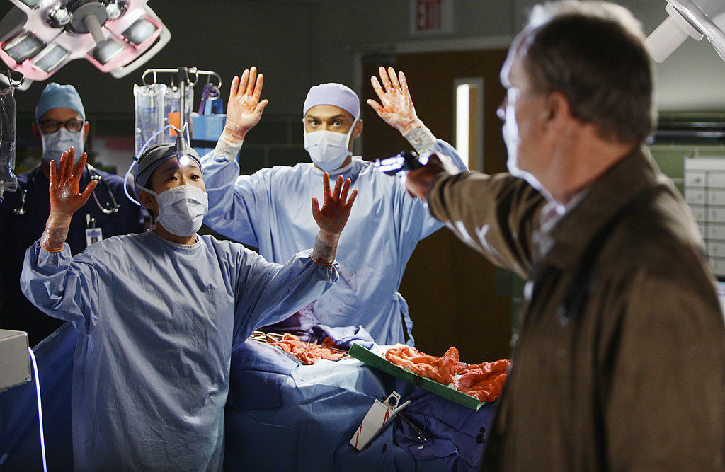 The shooter pointing the gun at Cristina and Jackson in the OR with Derek open on the table.