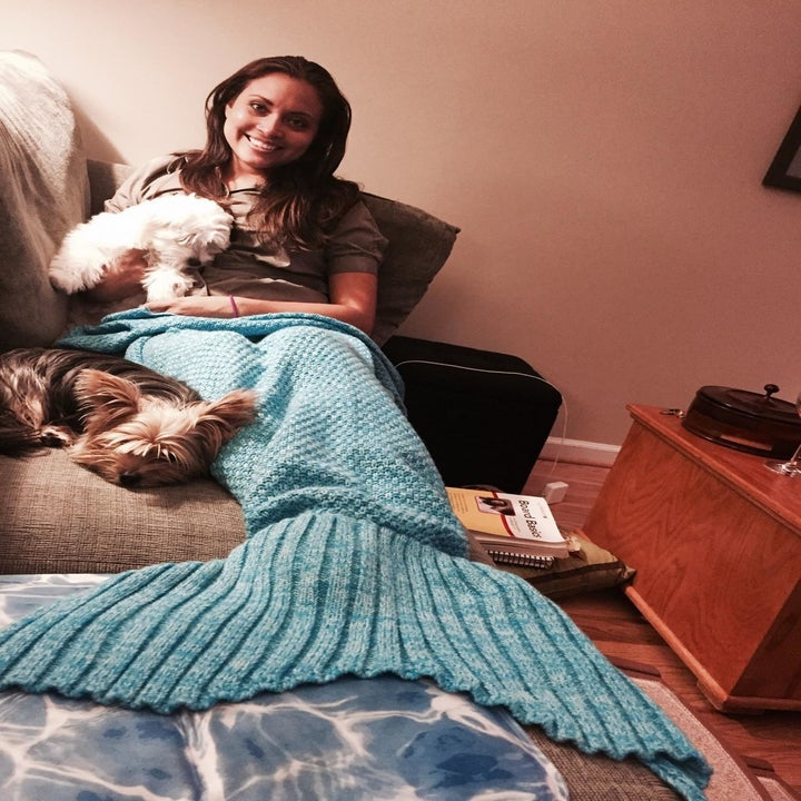 Reviewer snuggles with dog under a mermaid-shaped blue blanket at home