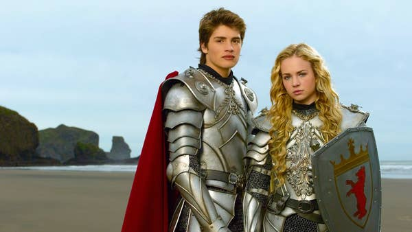 Will Wagner (Gregg Sulkin) and Allie Pennington (Britt Robertson) stand in knight armor on the beach.