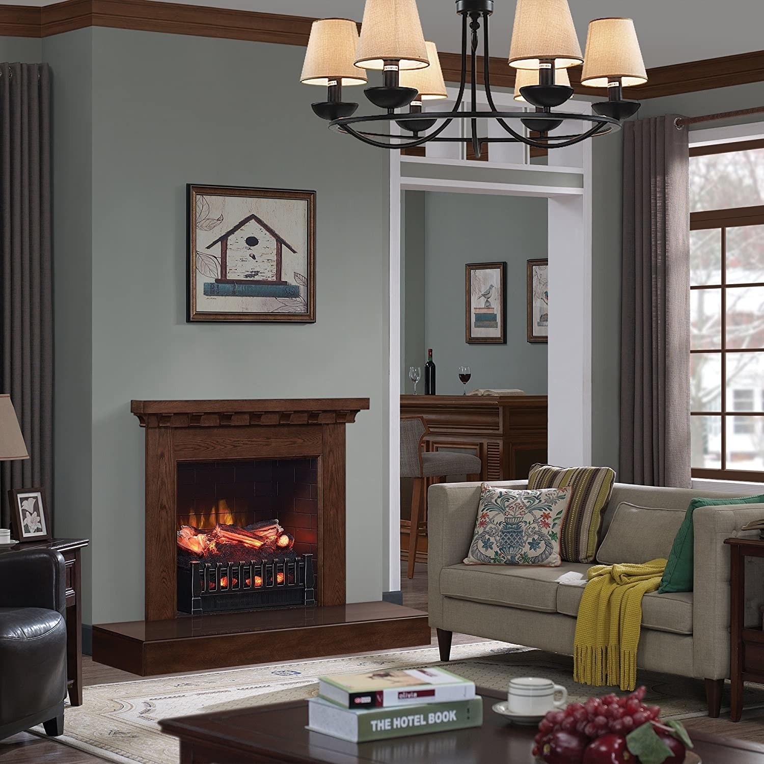 Electric fireplace in front of living room decorated with a cozy gray couch, armchair, and coffee table