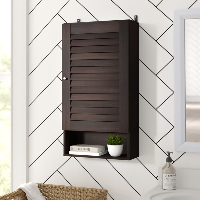 the ebern designs Espresso Dickens Wall Mounted Over-The-Toilet Storage mounted on a bathroom wall