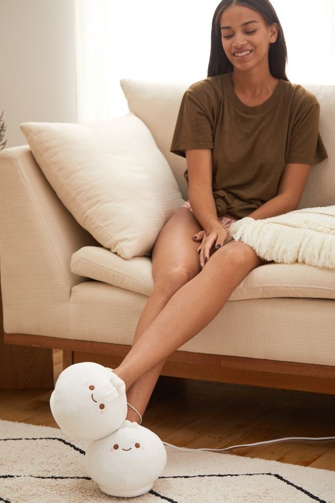 Model wears dumpling-shaped heated slippers while sitting on a couch