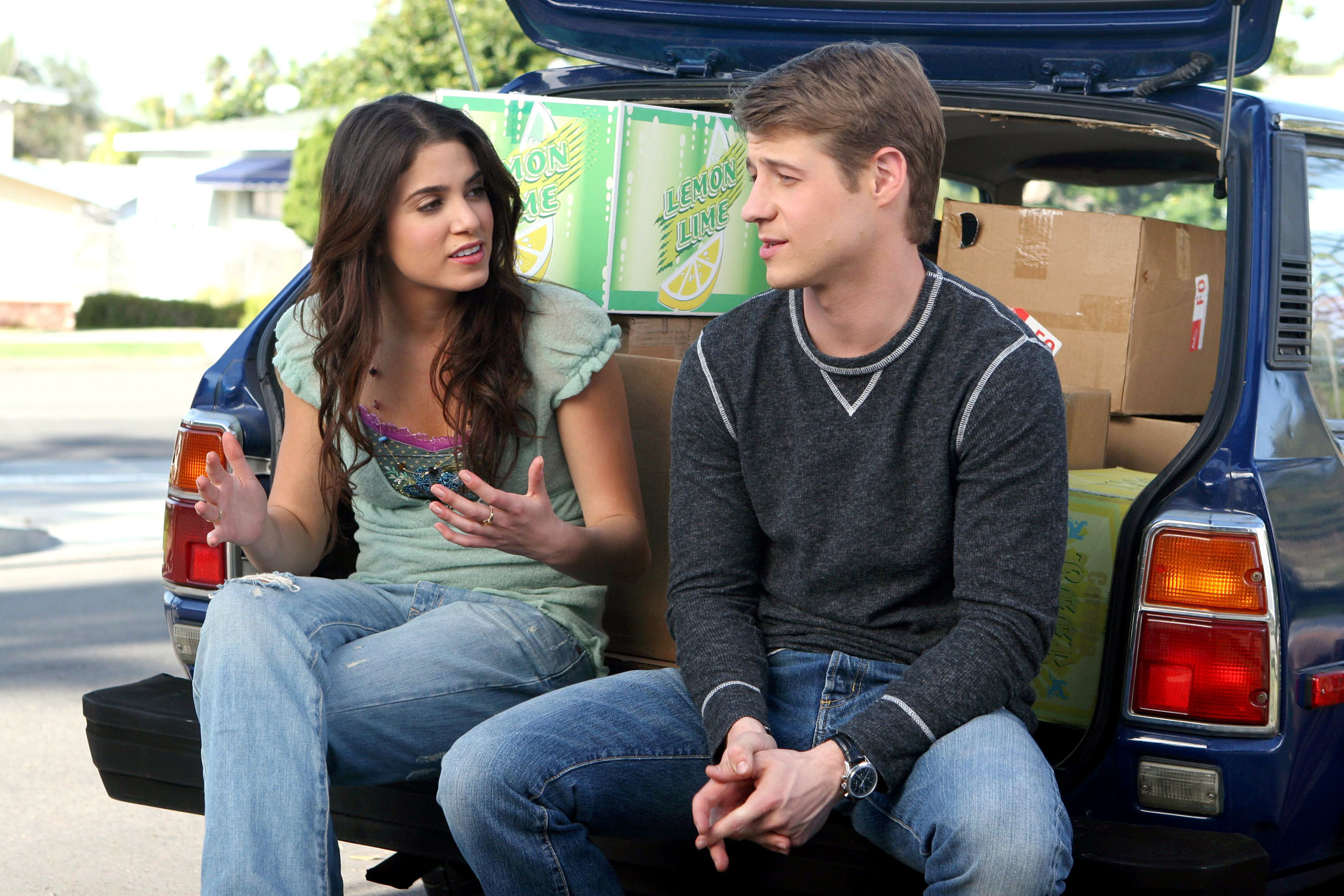 Sadie and Ryan sitting on the back of a car