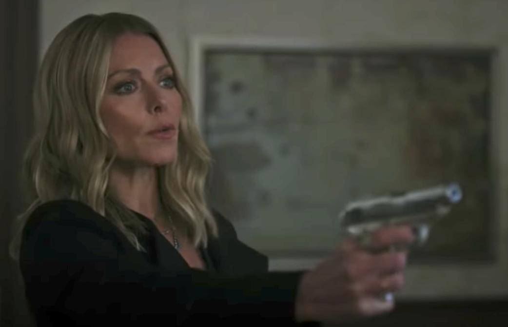 Kelly holding a gun