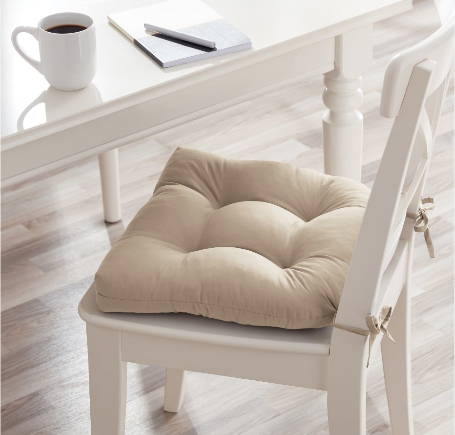 Beige cushion on white wooden chair