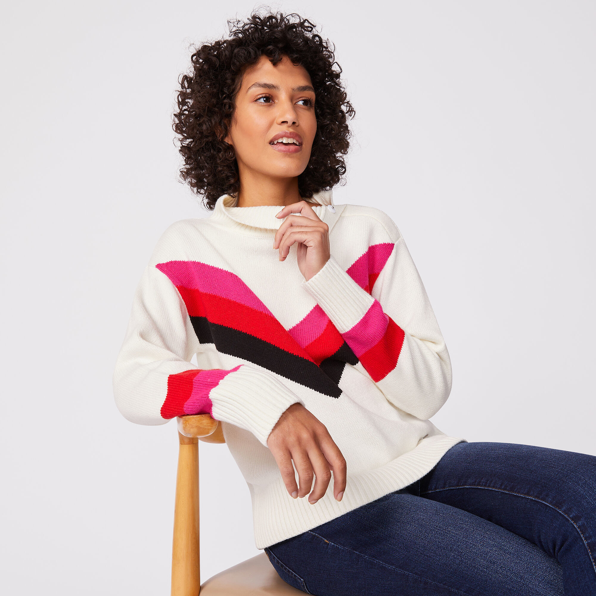 """Model wearing white sweater with a pink, red, and blue striped """"v"""" that meets in the center and extends to each shoulder"""