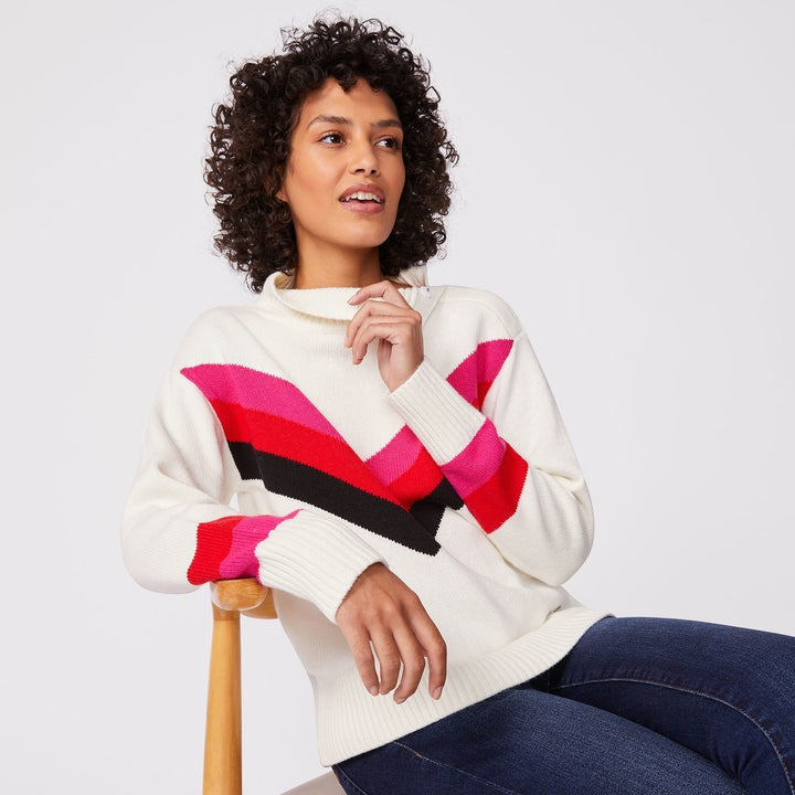 "Model wearing white sweater with a pink, red, and blue striped ""v"" that meets in the center and extends to each shoulder"