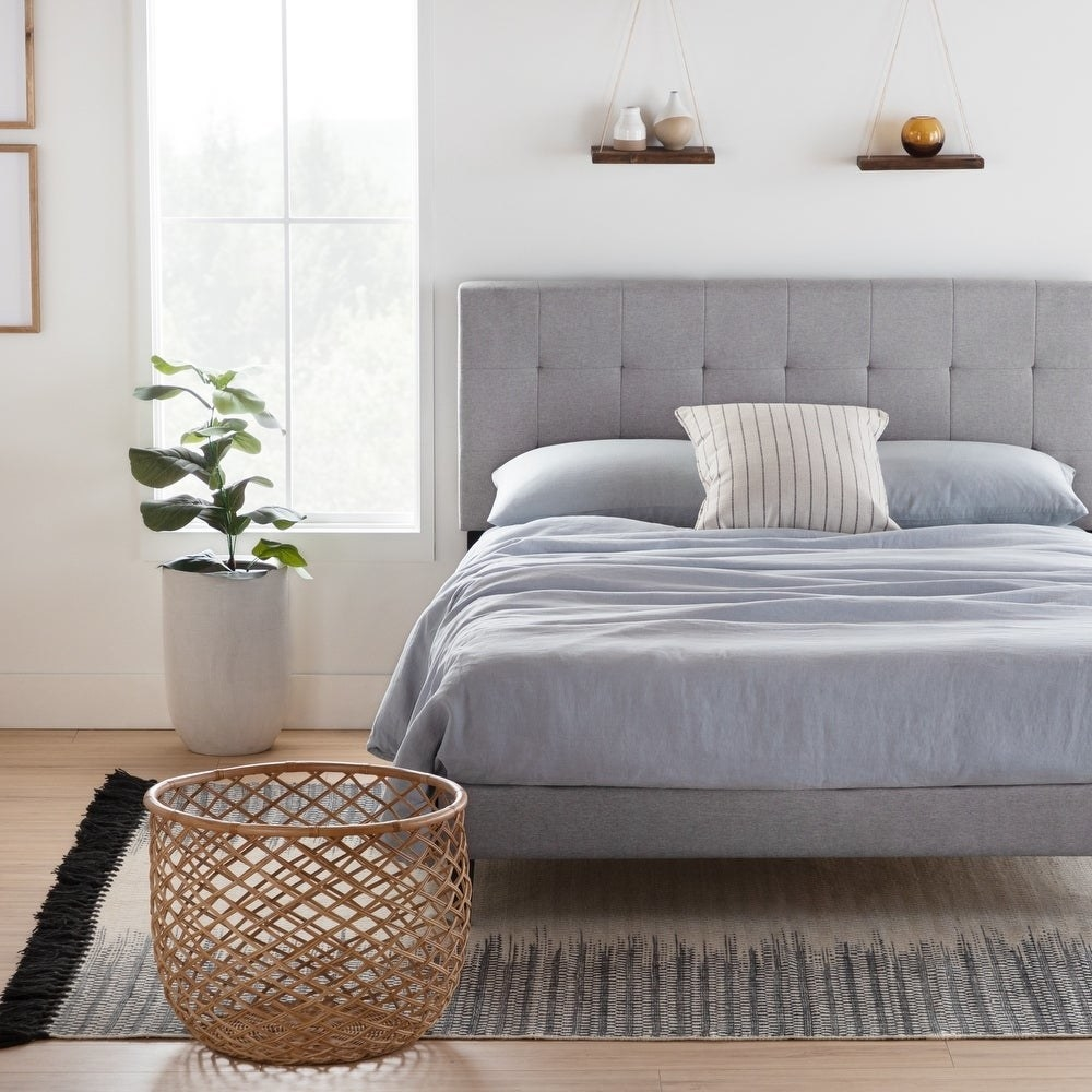 grey bed with tufted headboard