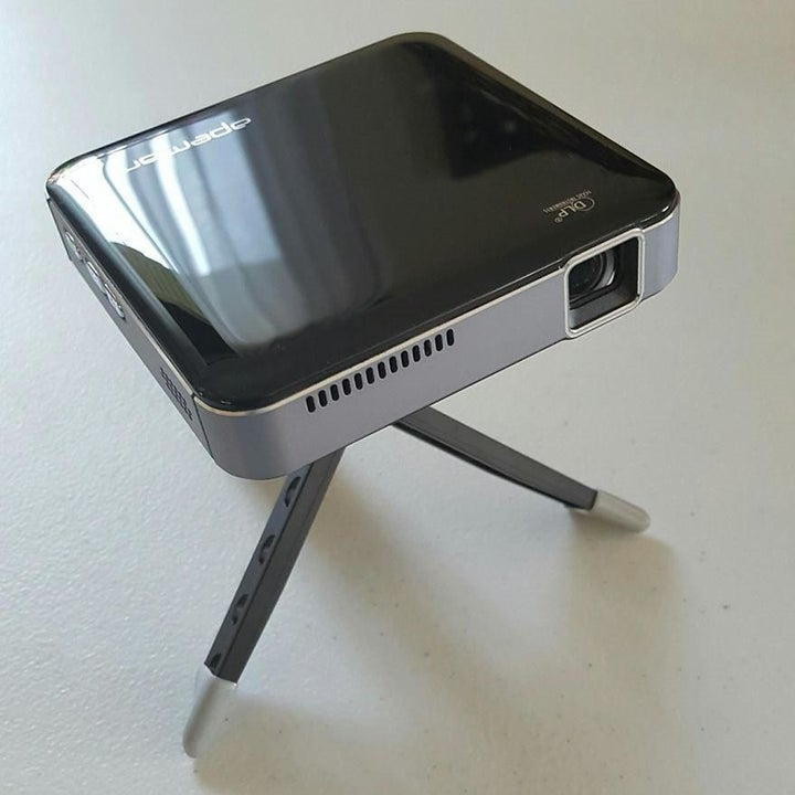 A reviewer photo of the projector mounted on the included tripod stand