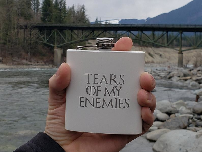 A person holding a flask that says tears of my enemies