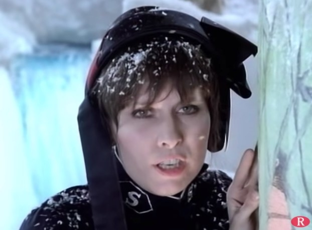 Chriss Hynde wearing a dark bonnet with fake snow on her head and shoulders
