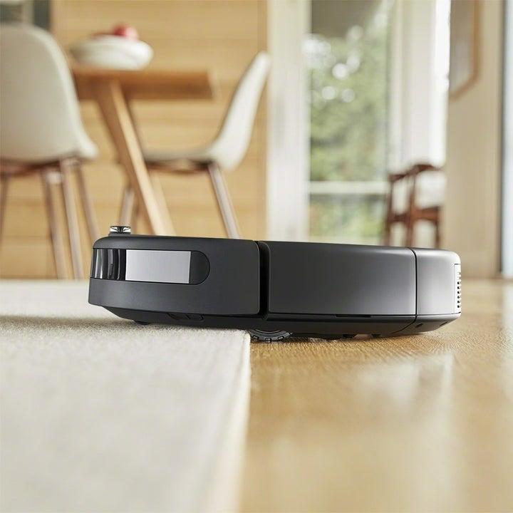 An iRobot Roomba Robot Vaccum rolling from hardwood floor to carpet