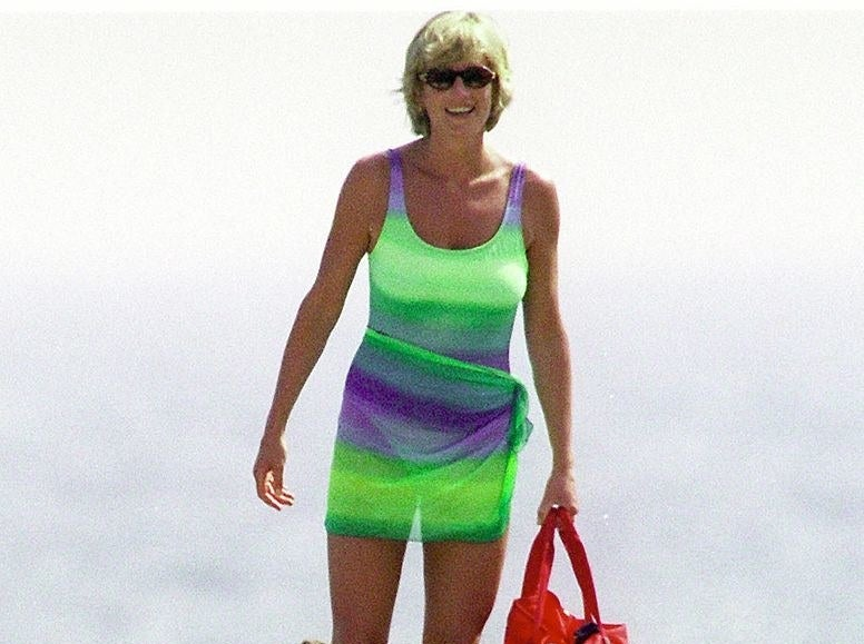 Princess Diana smiling in a bathing suit, a coverup tied around her waist, and sunglasses