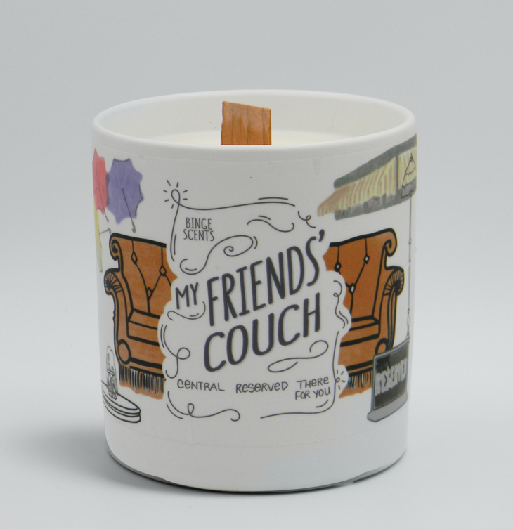 "The candle with an illustration of a brown couch, and other illustrations from the show around it and the words ""My Friends' Couch"" on it"