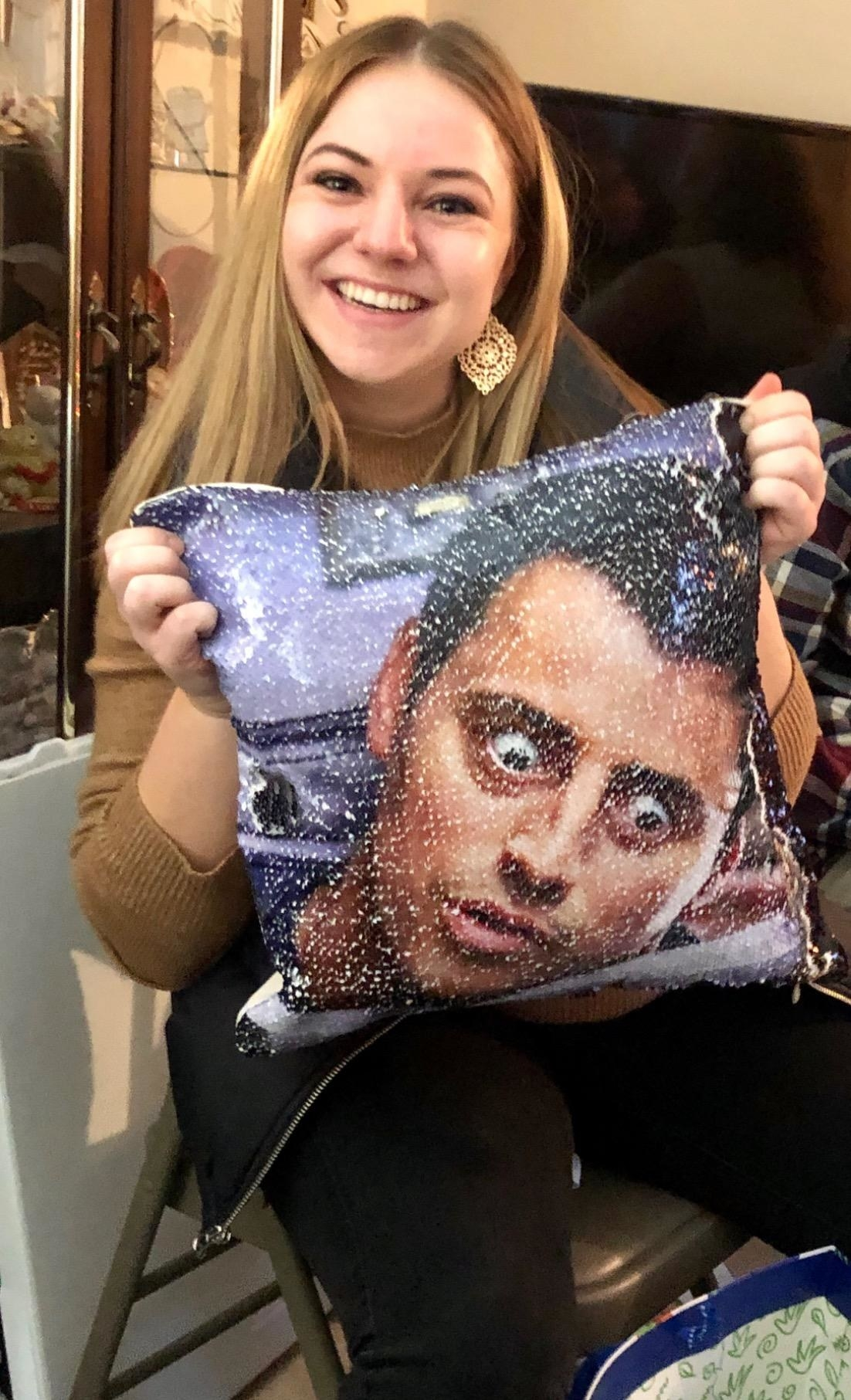 Reviewer holding the pillow with a picture of Joey's face in sequins on it