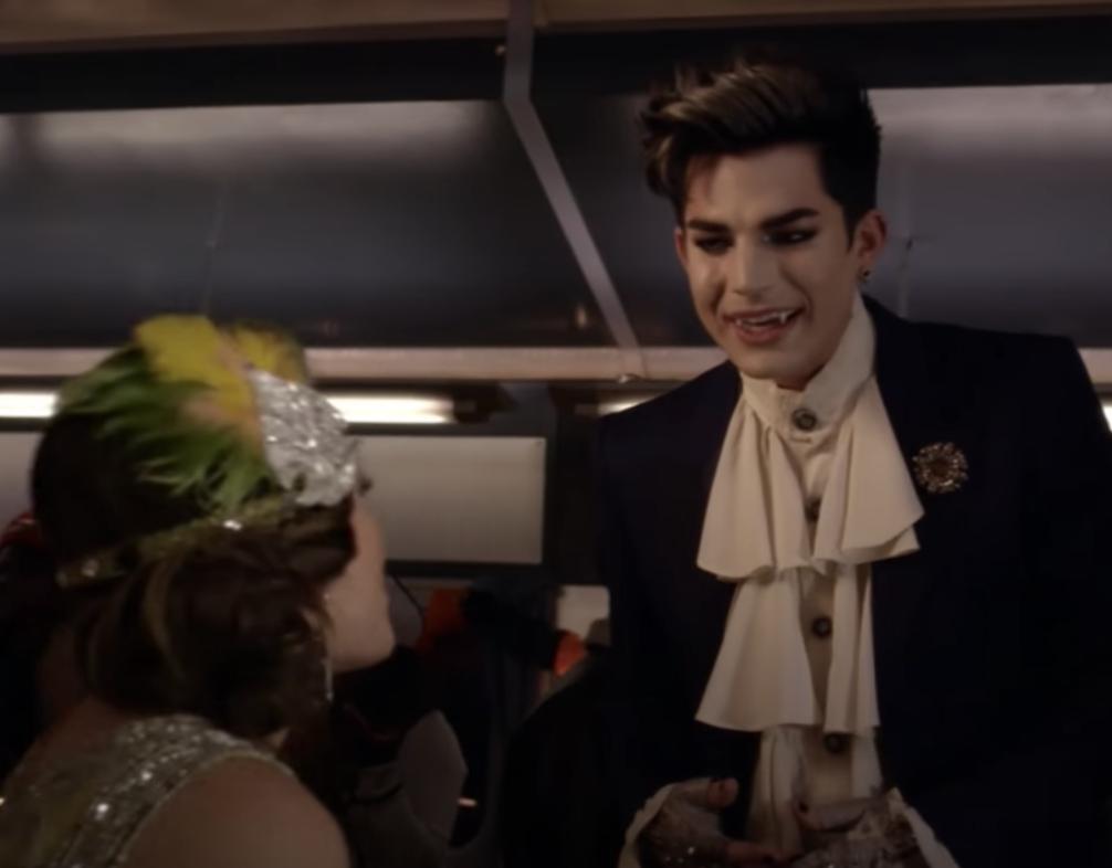 Adam, dressed as a vampire, talks to Aria