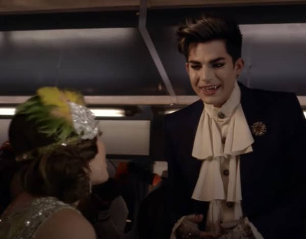 Adam, dressed as a vampire, talks to Aria