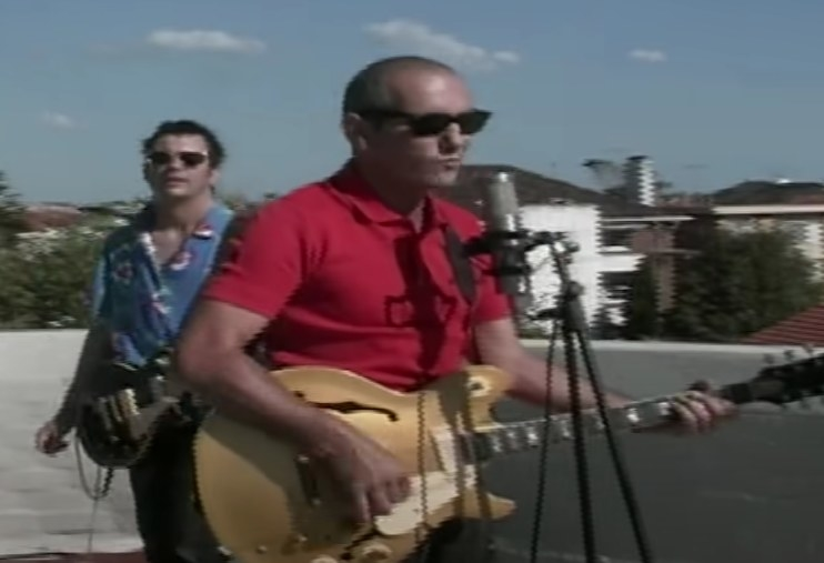 Paul Kelly playing a guitar and singing into a microphone while standing on a rooftop, with a guitarist standing behind him