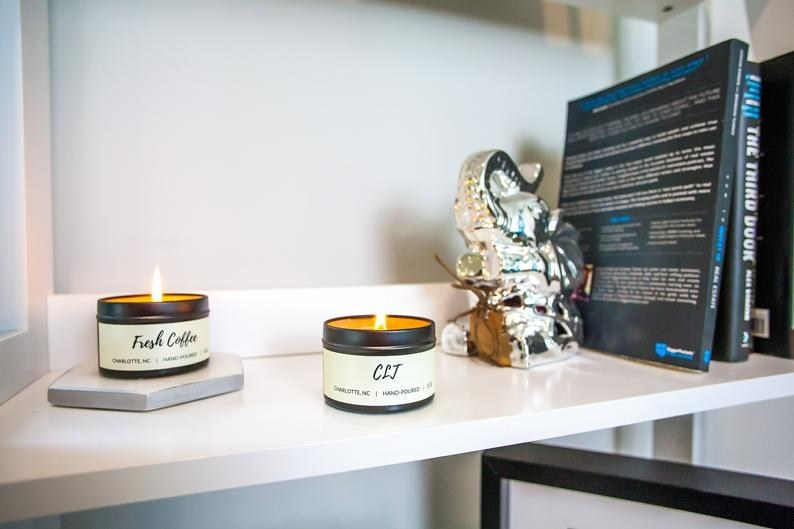 "Tin soy candles that say ""Fresh Coffee"" and ""CLJ"" on a white shelf adorned with elephant bookends and novels"