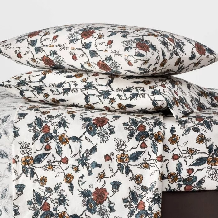 Red and blue floral flannel sheets with pillows stacked on top of a bed