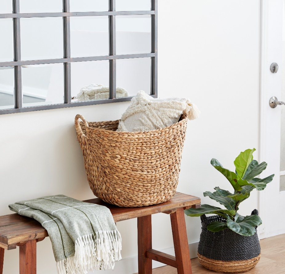 Wicker basket holding throw pillow on top of wooden bench