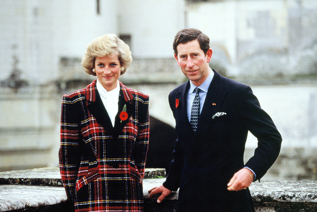 Princess Diana in a blazer with a poppy pin posing next to Prince Charles