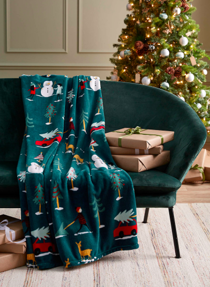 A holiday-themed fleece blanket draped on a velvet couch next to wrapped gifts