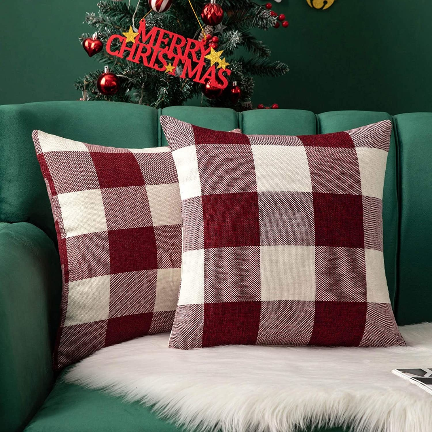 A pair of pillows covered in plaid cases on a velvet couch