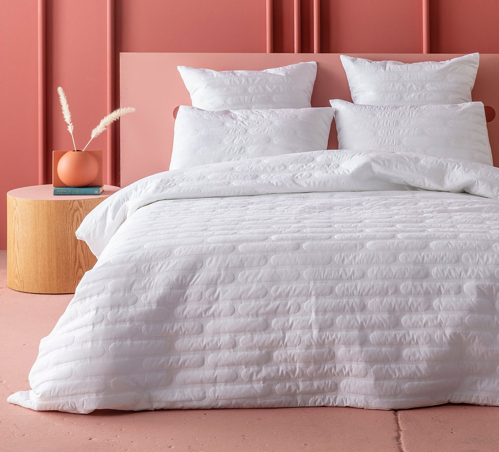 A duvet cover with a puffy quilted pattern on a bed with four pillows