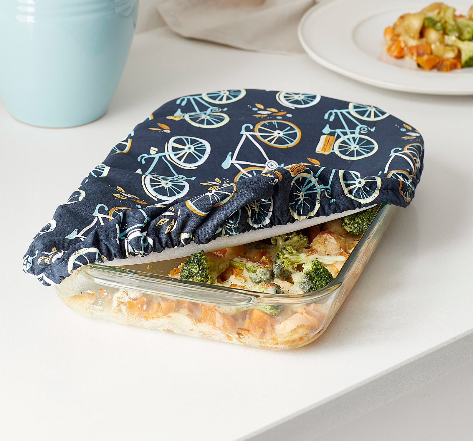 A glass dish pan with a fabric cover over it