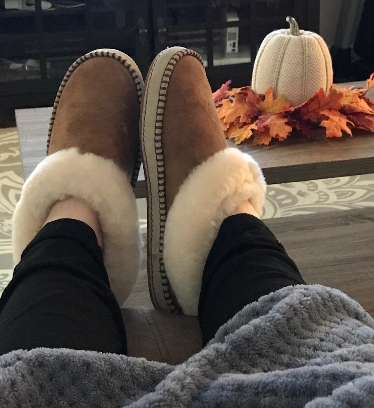 A reviewer wearing the slippers in chestnut