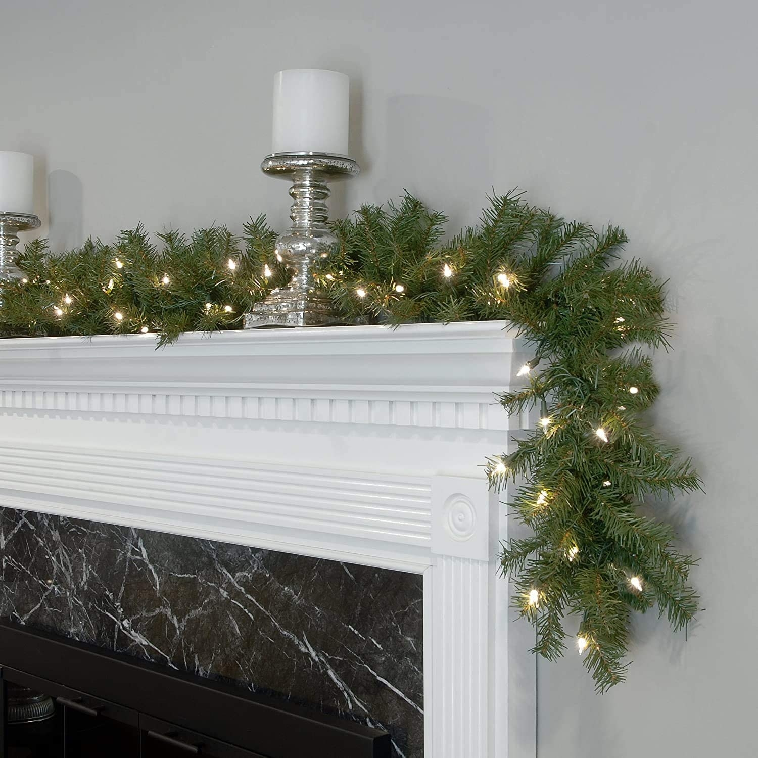 A close up of a pre-lit garland draped over a fireplace mantlepiece