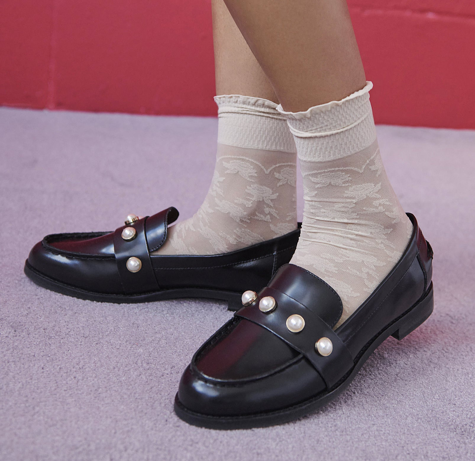 A person wearing leather loafers with pearls across the top