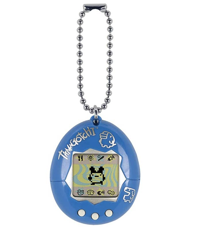 A tamagotchi handheld device with a character in the center of its screen