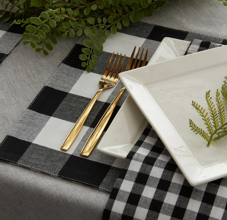 Black and white plaid placemat under gold fork and knife
