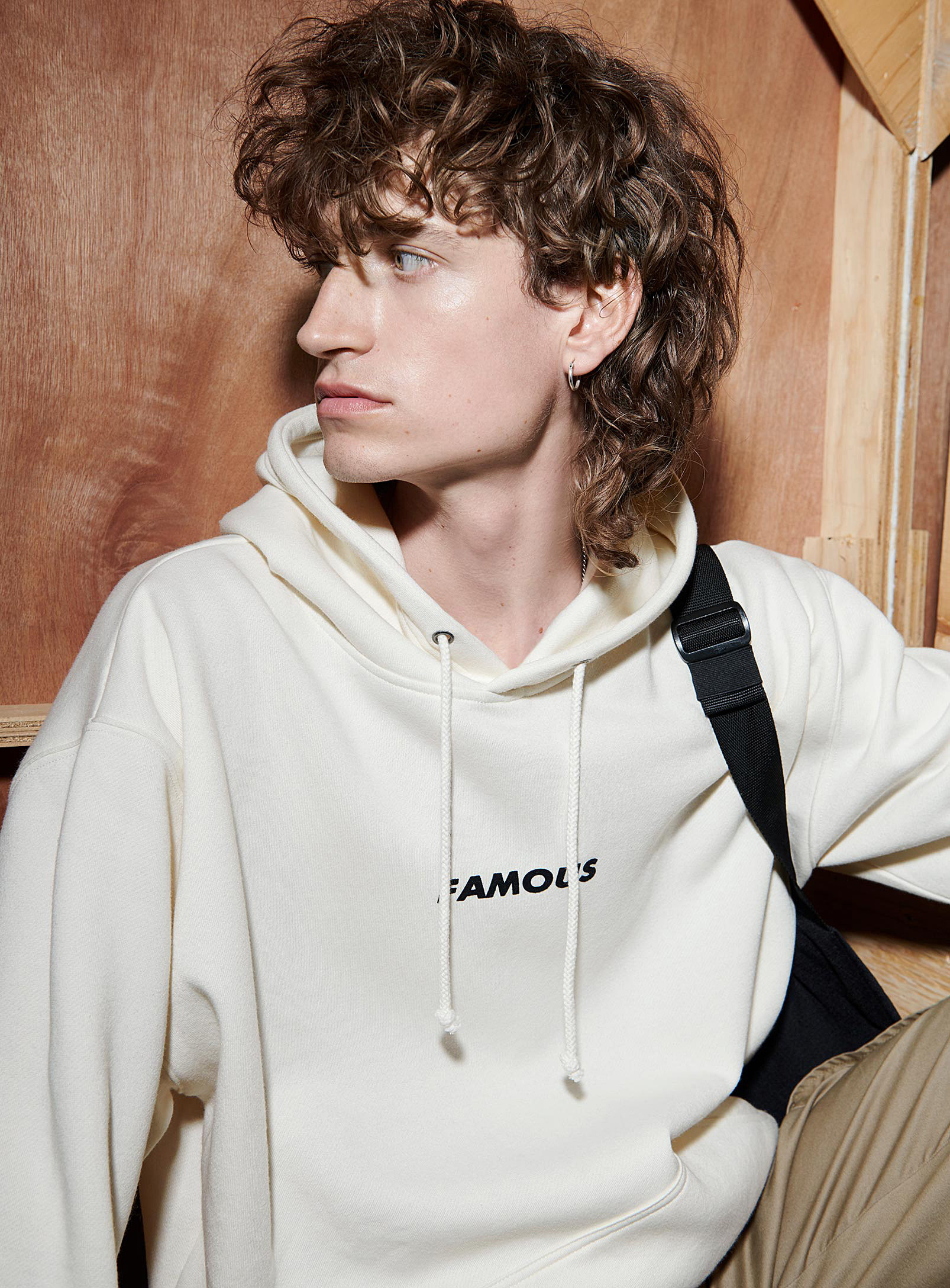 A person wearing a hoodie that says famous on the chest